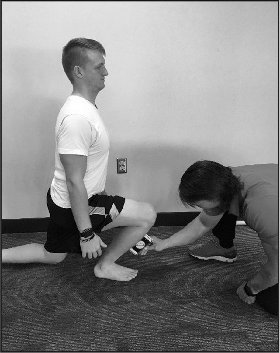 Half Kneeling Dorsiflexion Test. The participant assumes a half kneeling position. Keeping the front heel down, the participant advances the front knee as far as possible over the front foot. The tester measures the degrees using an inclinometer.