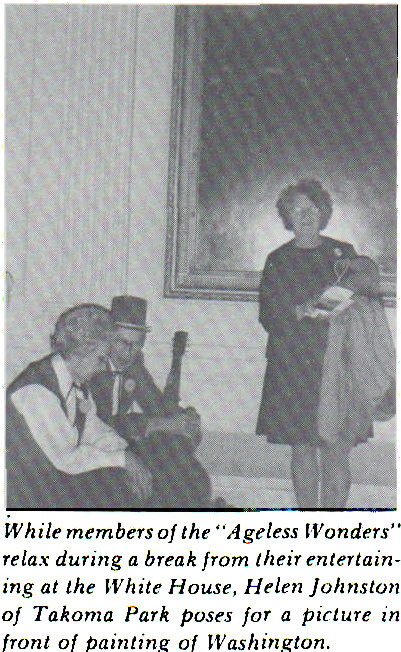 """While members of the """"Ageless Wonders"""" relax during a break from their entertaining at the White House, Helen Johnston of Takoma Park poses for a picture in front of painting of Washington."""