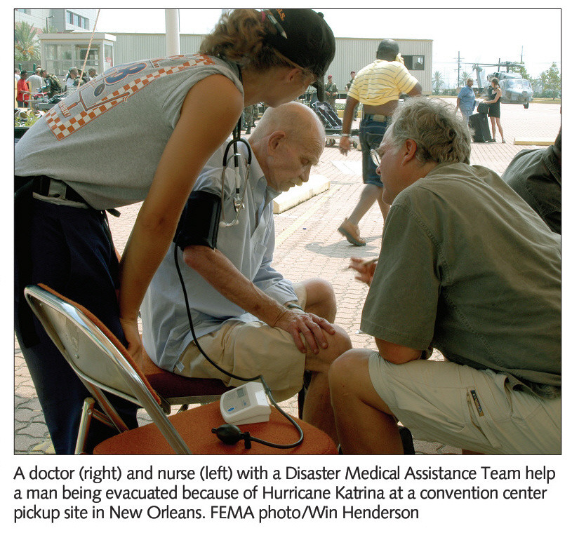 A doctor (right) and nurse (left) with a Disaster Medical Assistance Team help a man being evacuated because of Hurricane Katrina at a convention center pickup site in New Orleans. FEMA photo/Win Henderson