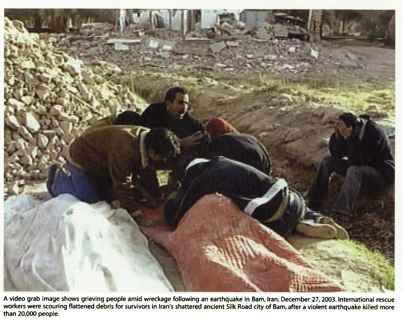 A video grab image shows grieving people amid wreckage following an earthquake in Bam, Iran, December 27, 2003. International rescue workers were scouring flattened debris for survivors in Iran's shattered ancient Silk Road city of Bam, after a violent earthquake killed more than 20,000 people.