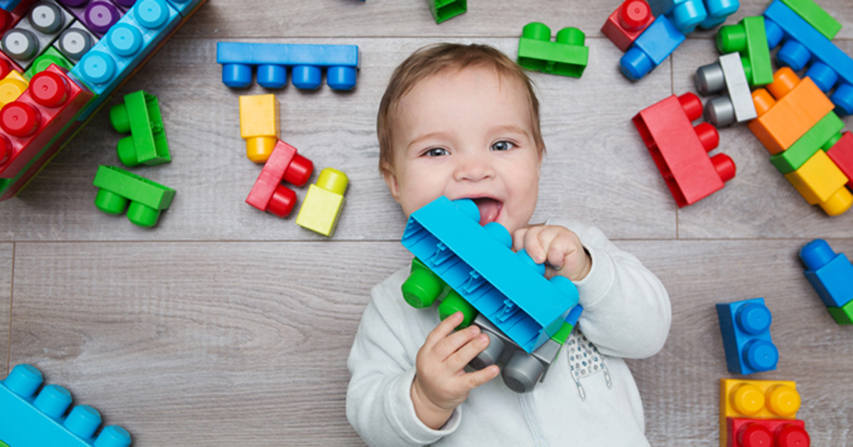 Baby with toy block in mouth