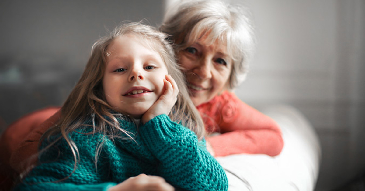 Grandmother sitting on couch with grandchild